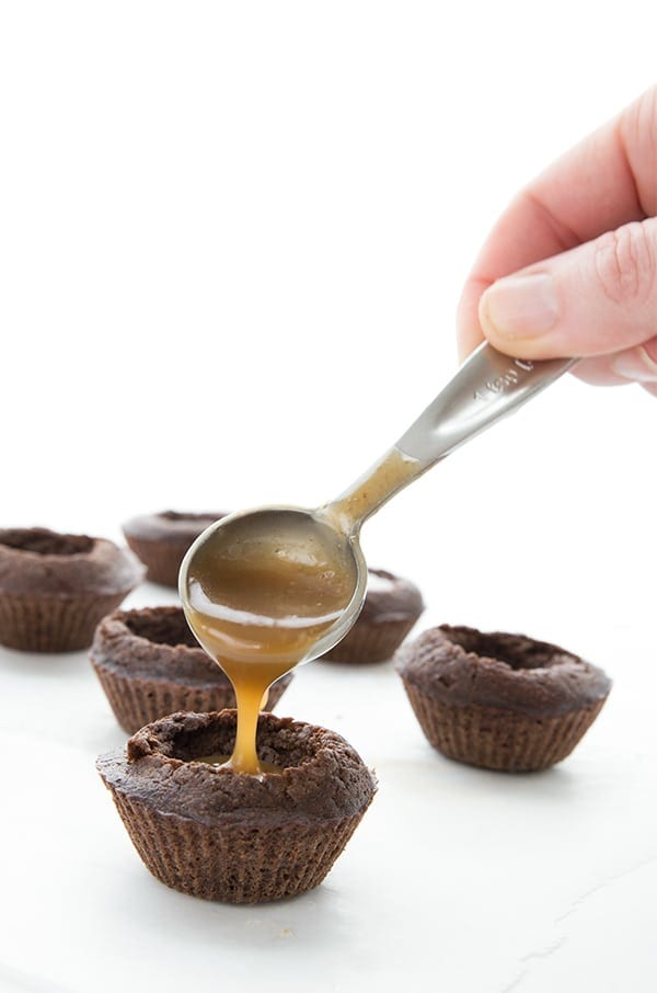 Pouring sugar free caramel sauce into little low carb brownie bites