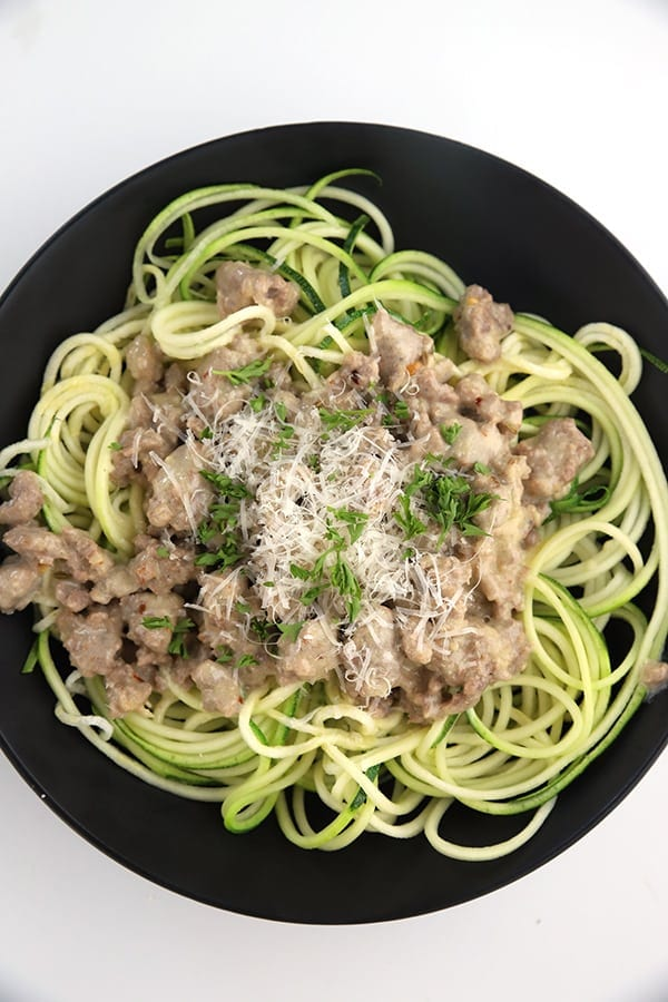 Zucchini noodles topped with low carb sausage alfredo sauce in a black bowl