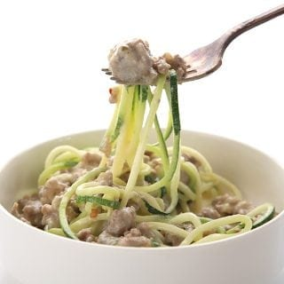 Easy keto alfredo sauce with sausage and zucchini noodles in a bowl and on a fork.