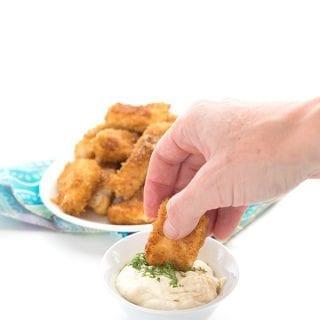 Dipping a fish stick into garlic dill mayo