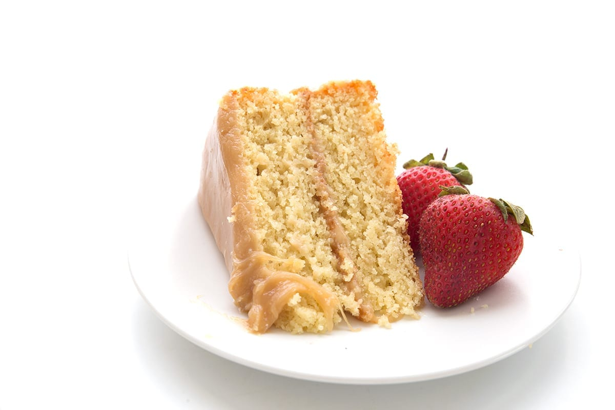 A slice of keto caramel cake a white plate with two strawberries