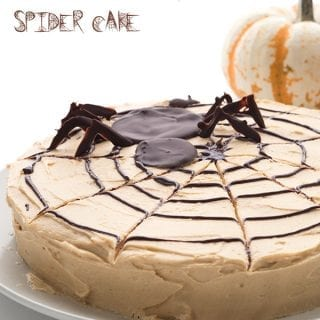 Keto Spider Web Cake on a plate with pumpkins in the background
