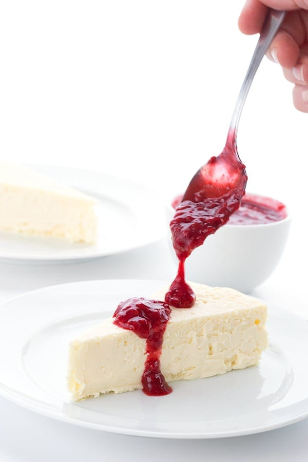 Sugar free raspberry sauce being drizzled over new york style keto cheesecake