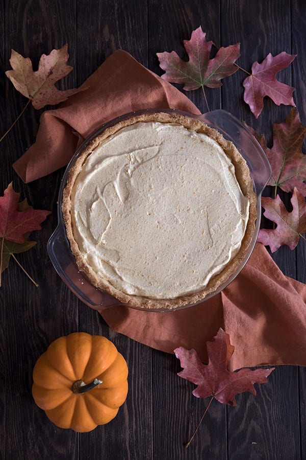 Top down photo of keto pumpkin pie with an orange napkin, maple leaves, and mini pumpkins around it