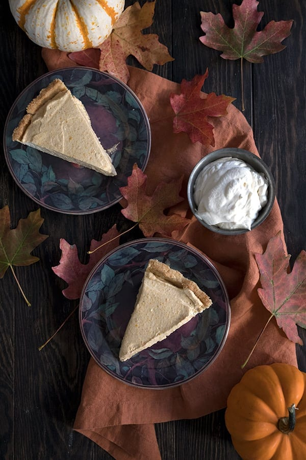 Top down photo of slices of pumpkin cream pie on a brown table with whipped cream in a bowl