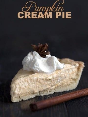Keto Pumpkin Cream Pie - a slice of pie on a dark table with whipped cream and cinnamon sticks.
