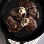 Top down photo of tenderloin steaks in a cast iron skillet