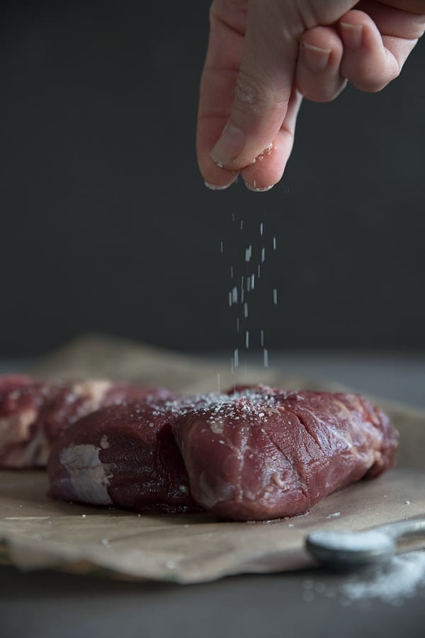 Coarse salt being sprinkled on beef tenderloin steaks