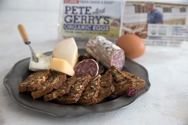 A cheese and salami plate with keto cranberry hazelnut crisps