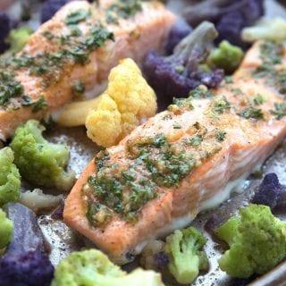 Two salmon filets on a sheet pan with veggies