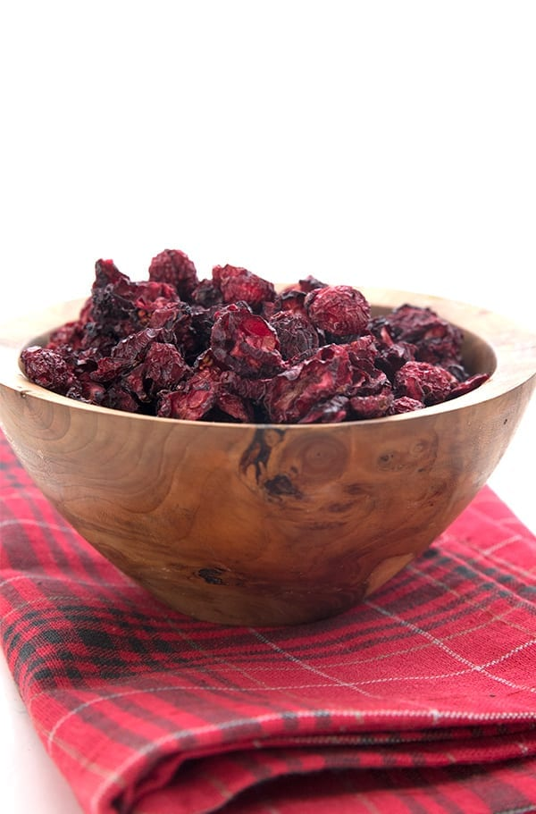Keto dried cranberries in a wooden bowl on a red plaid napkin