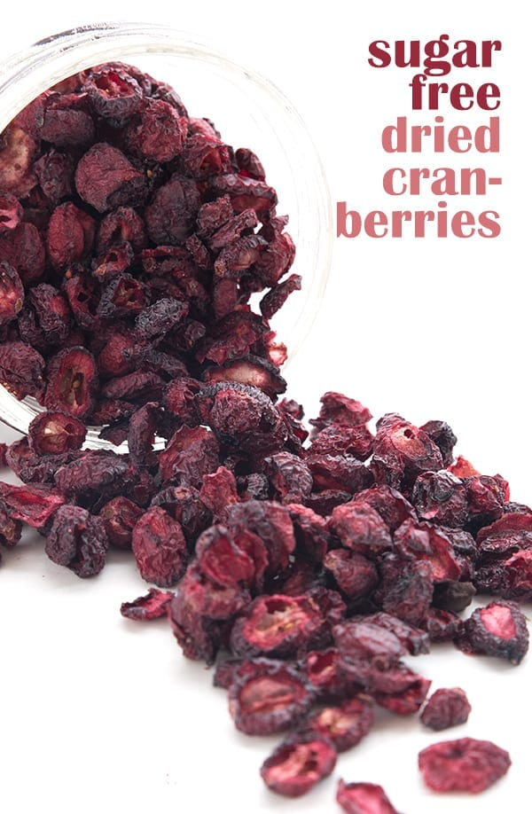 Easy homemade dried cranberries spilling out from a jar