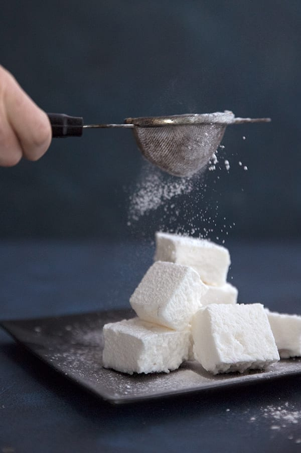 Powdered sweetener being dusted over sugar free marshmallows