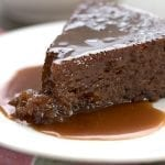 A slice of low carb sticky toffee pudding on a white plate