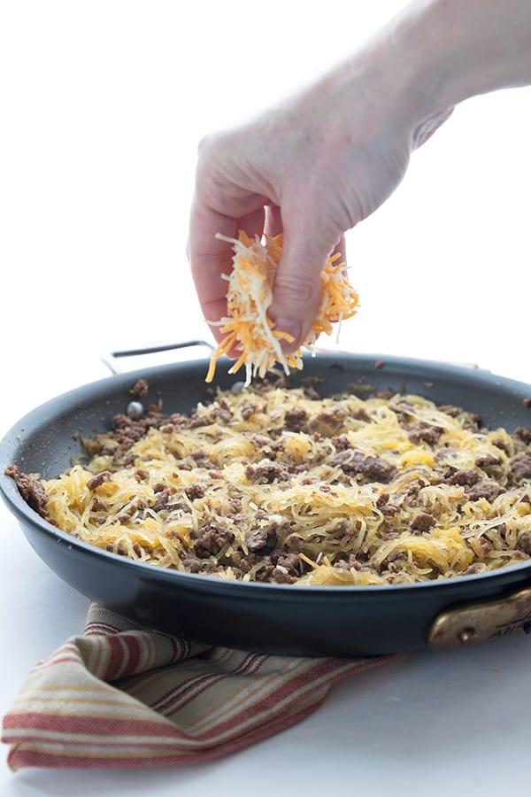 Sprinkling cheese over a spaghetti squash casserole