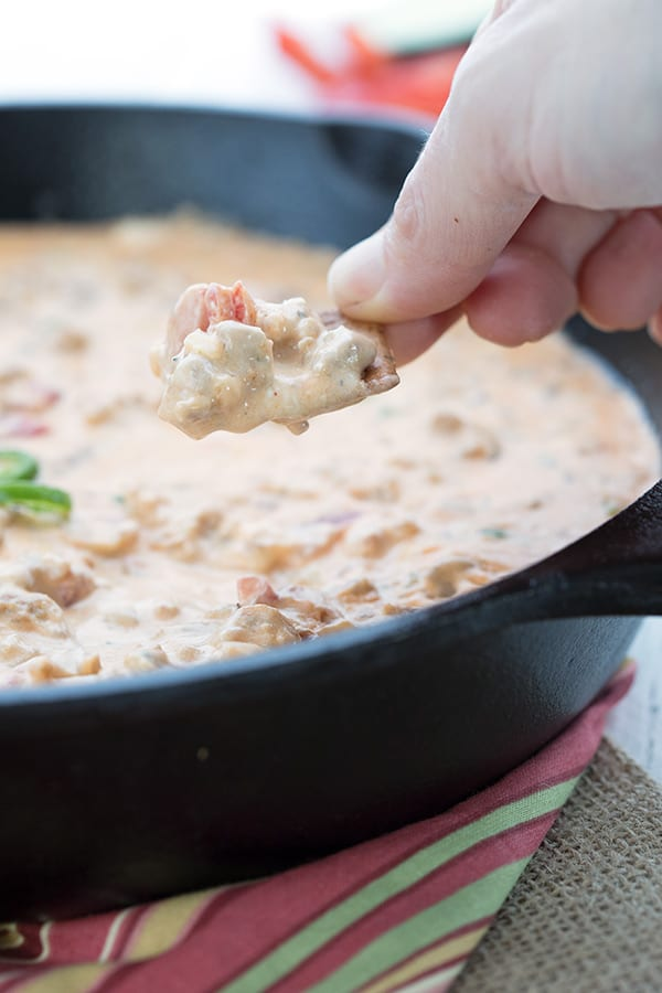 Low Carb cracker being dipped into spicy sausage dip