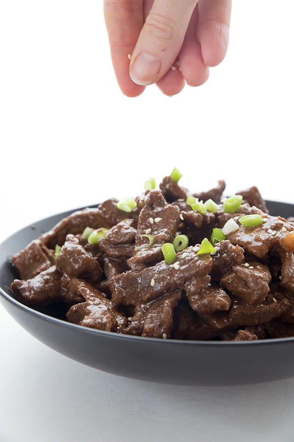 Sesame seeds being sprinkled on keto mongolian beef in a black bowl