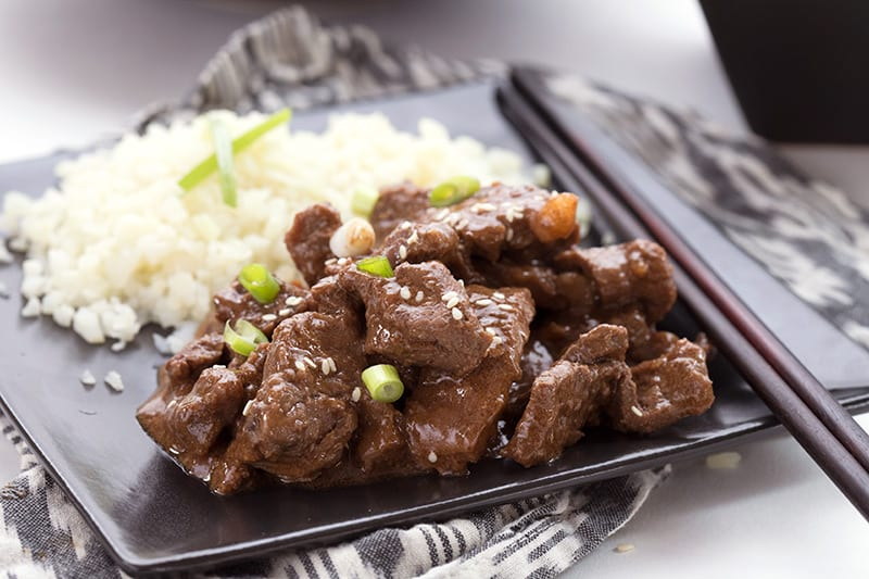 Easy slow cooker Mongolian Beef on a black plate with chopsticks