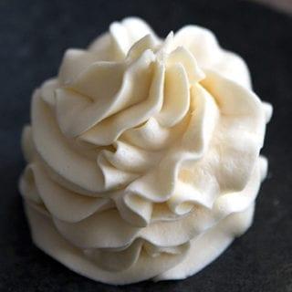 Keto vanilla frosting piped into a dark bowl