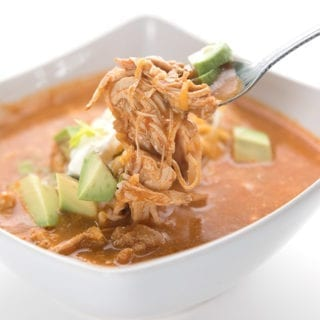 A spoonful of chicken enchilada soup hovering over the bowl