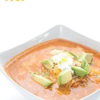 Easy Enchilada Soup in a bowl with cheese, sour cream and avocados