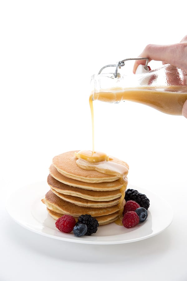 Low carb syrup pouring over a stack of keto pancakes