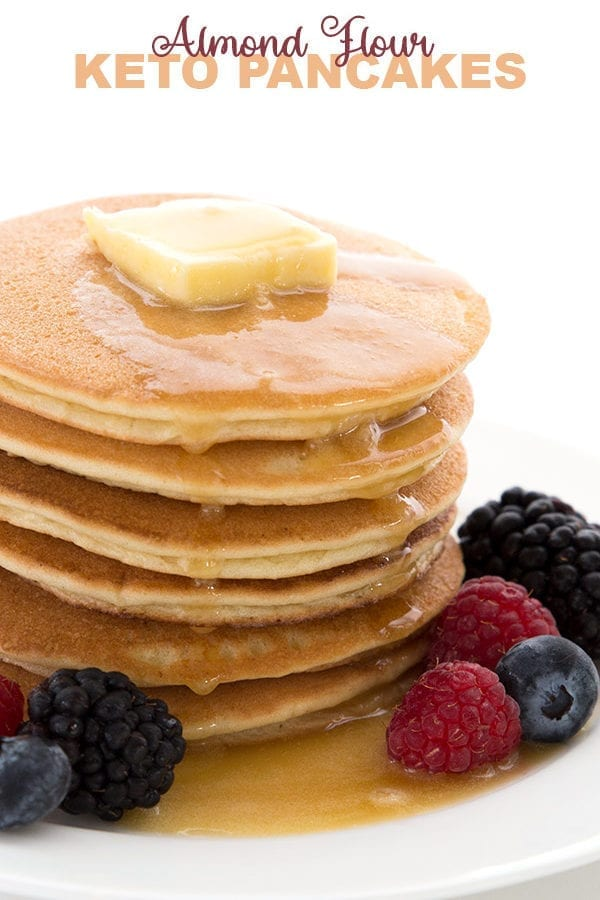 Keto Almond Flour Pancakes in a stack with berries and sugar free syrup