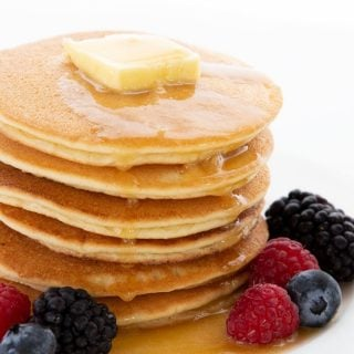 Titled image of a stack of keto pancakes on a white plate, with berries all around.