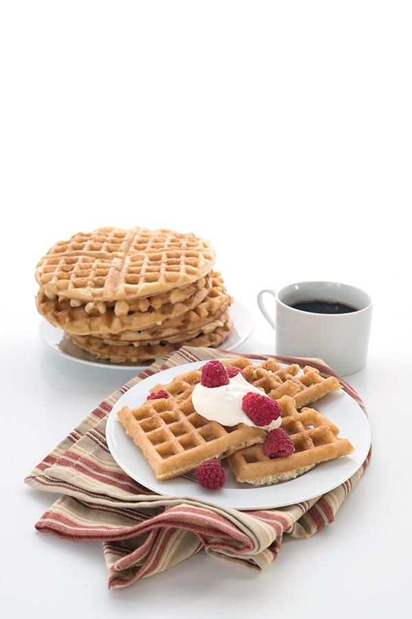 Almond flour waffles on a plate with whipped cream and berries