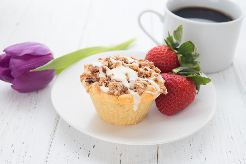 A coffee cake muffin on a plate with two strawberries
