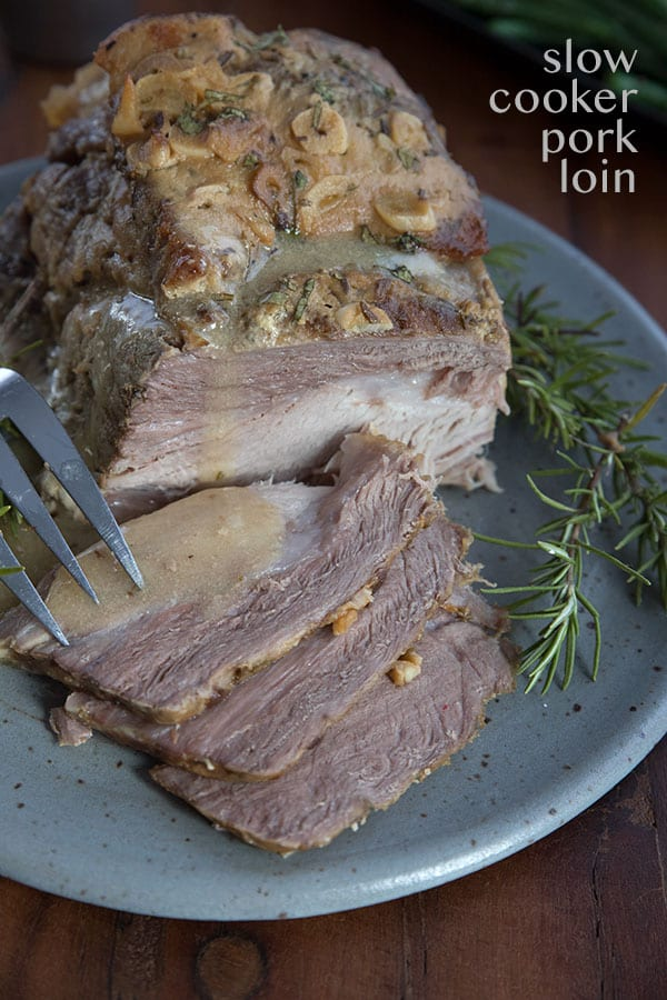 Easy slow cooker pork loin roast on a gray plate with sauce