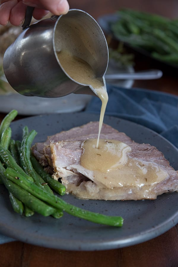 Drizzling sauce over slow cooker pork loin roast