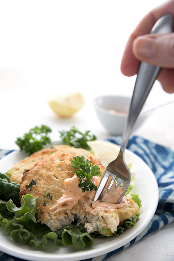 Taking a forkful of air fryer crab cakes