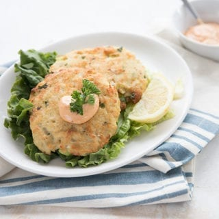 Two keto crab cakes on a white plate with a striped blue napkin