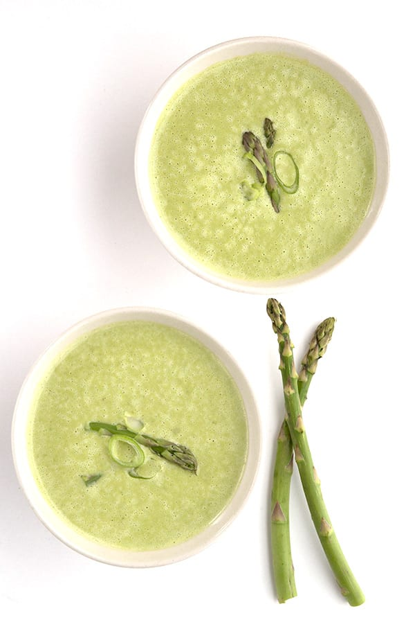 Top down photo of asparagus soup in two white bowls