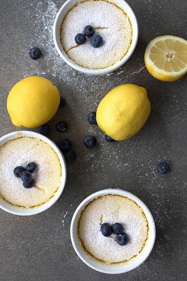 Top down photo of lemon pudding cakes with lemons and blueberries