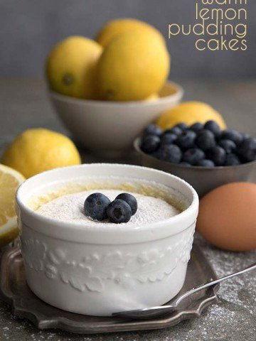 Warm Lemon Pudding Cake in a white ramekin with lemons in the background. Keto sugar-free recipe