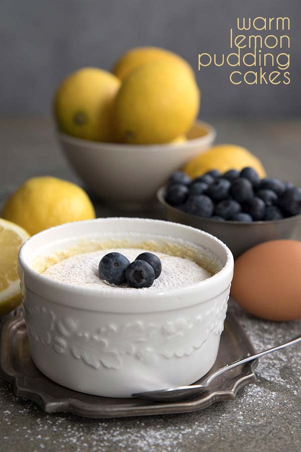 Warm Lemon Pudding Cake in a white ramekin with lemons in the background. Keto sugar-free recipe