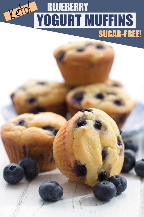 Keto blueberry muffins in a cluster with fresh blueberries. Titled image