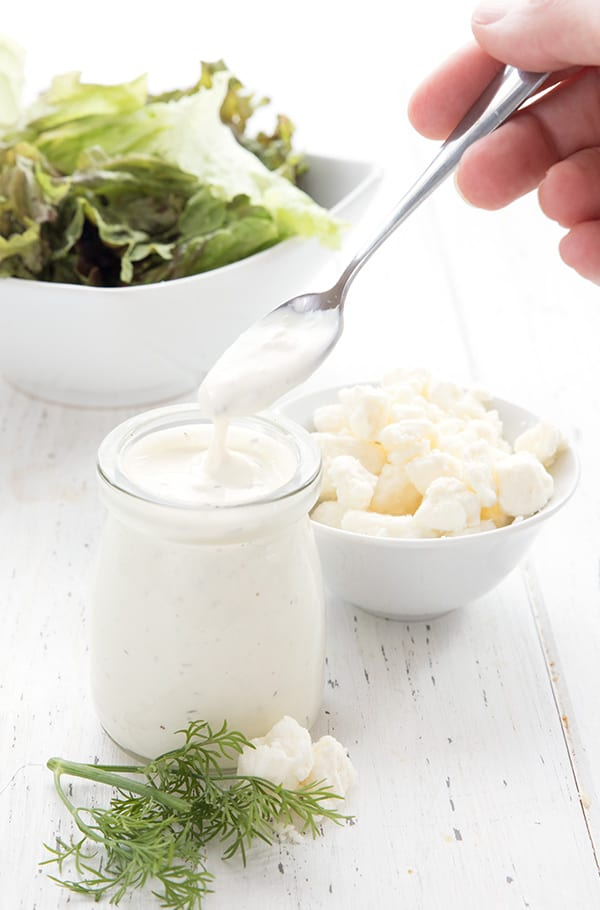 A small jar of keto salad dressing with salad in the background