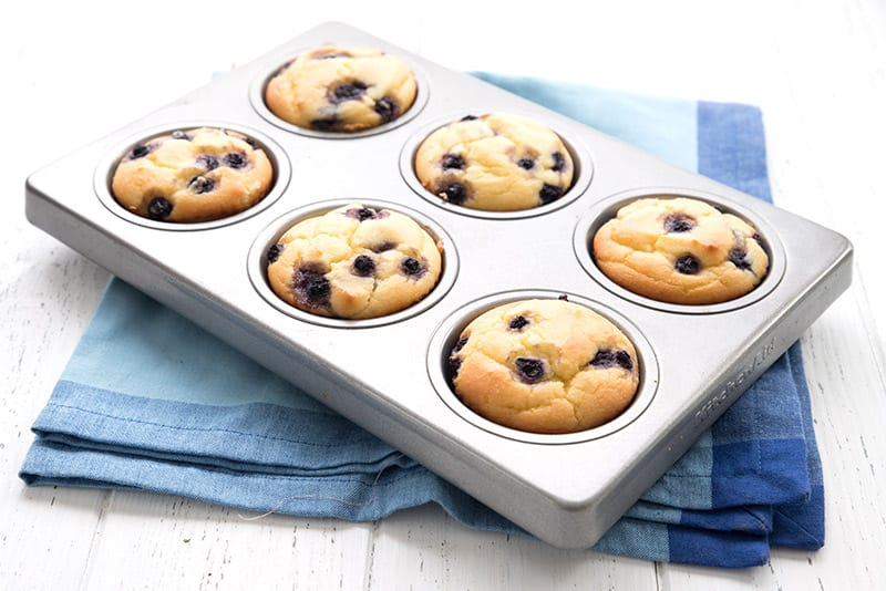 Blueberry yogurt muffins in a muffin pan on a blue napkin