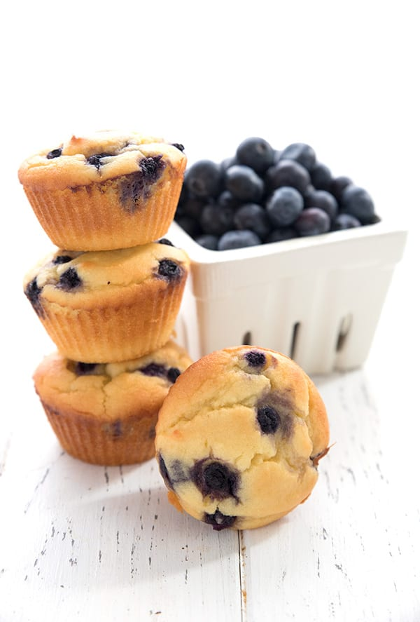 A stack of blueberry yogurt muffins in front of a pint of berries