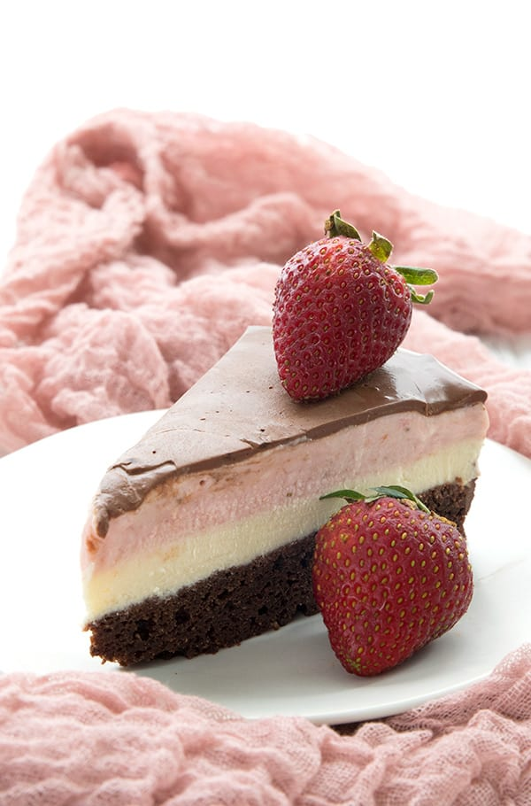 A slice of homemade keto ice cream cake with strawberries on a pink napkin