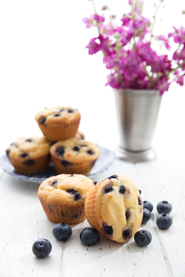 Keto yogurt muffins in a pile with flowers in the background
