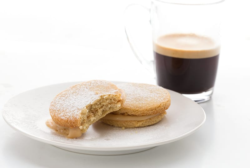 Two alfajores on a plate with a cup of espresso in behind.