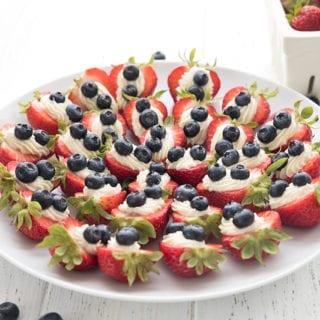 A platter full of patriotic cheesecake stuffed strawberries