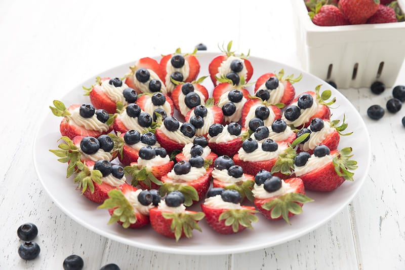 A platter full of patriotic cheesecake stuffed strawberries
