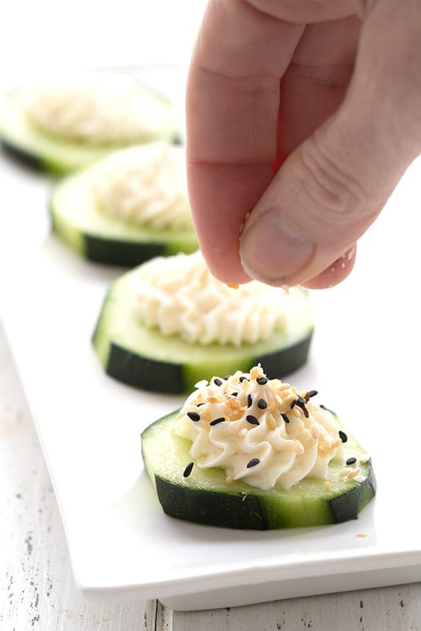 Sprinkling everything bagel seasoning onto cucumber cream cheese appetizers