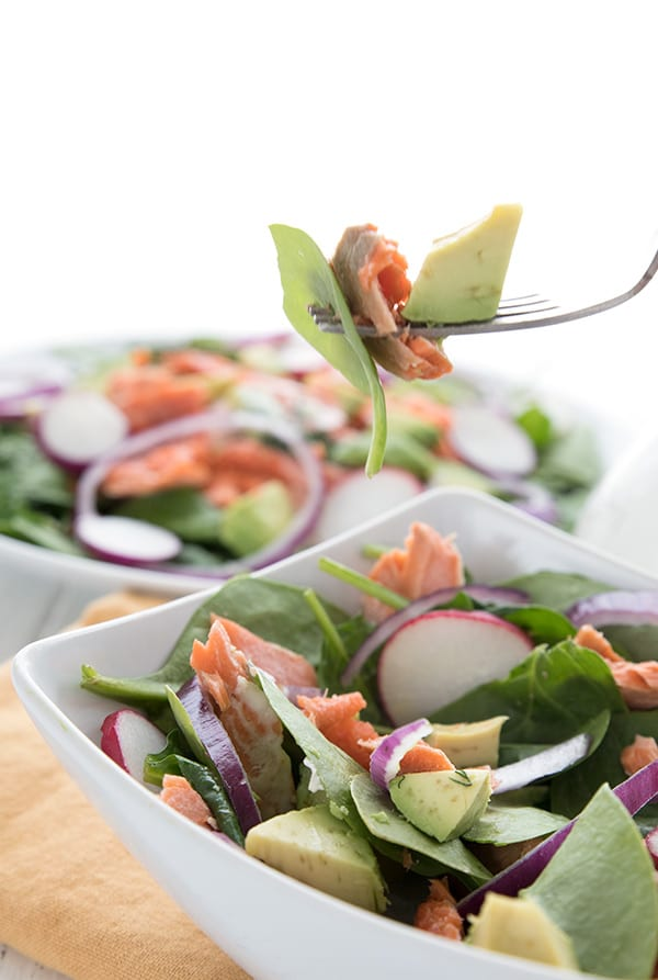 A fork holding up a bite of paleo salmon avocado salad