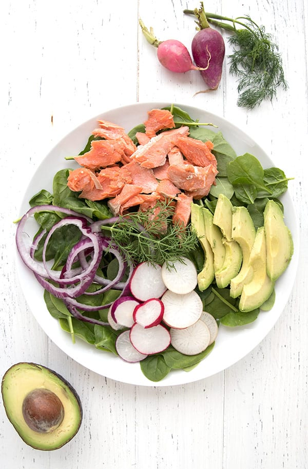 A large platter of spinach salad with salmon and avocado